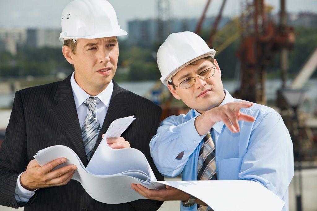 constructor y albañil revisando planos